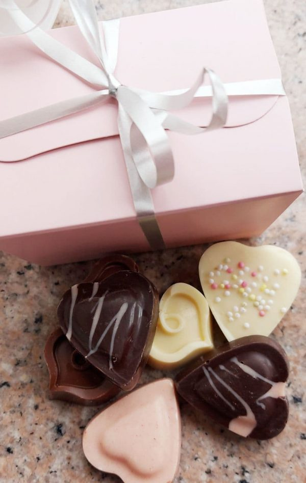 solid chocolate hearts in a pastel pink ballotin
